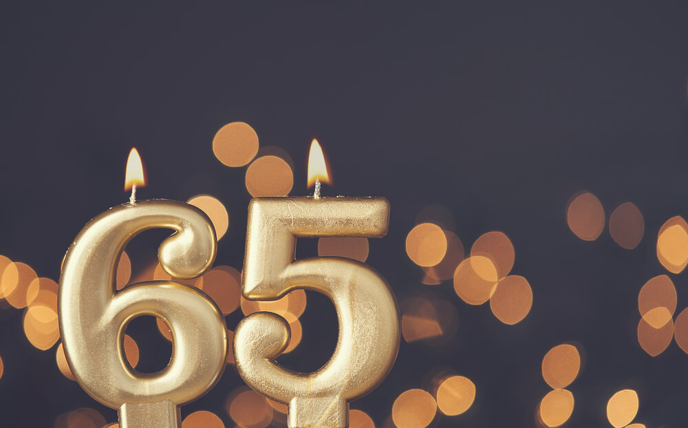 "golden ""65"" birthday candles that are lit up"