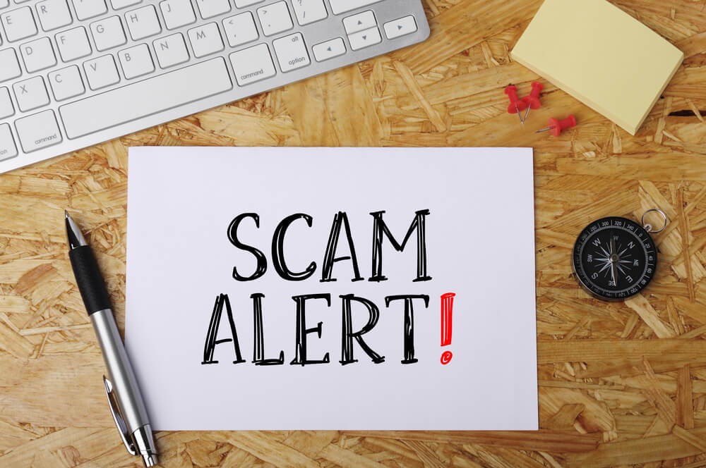 "a desk with a piece of paper that says ""scam alert"""