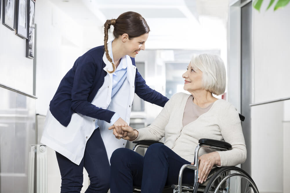 nurse holding hand with elderly woman in a wheelchair