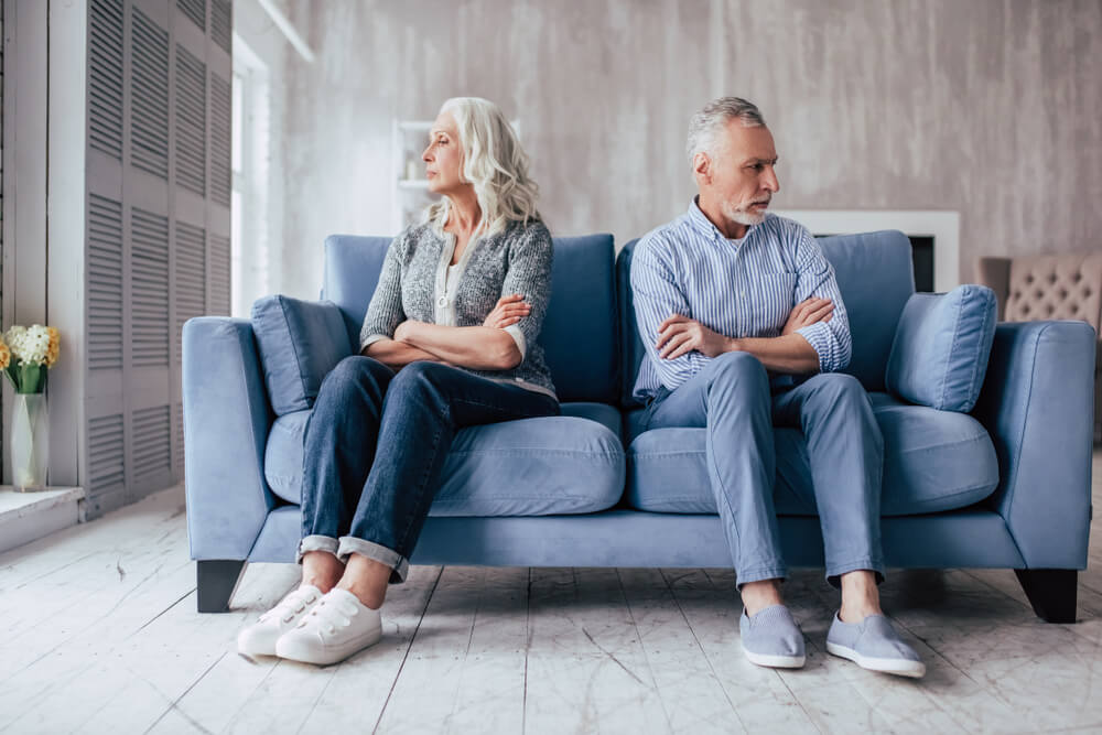 elderly man and woman sitting on a couch facing away from each other with their arms crossed