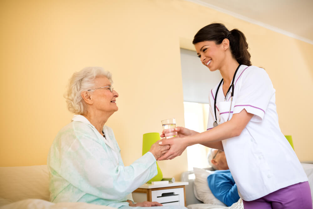 nurse giving elderly immobile woman a glass of water