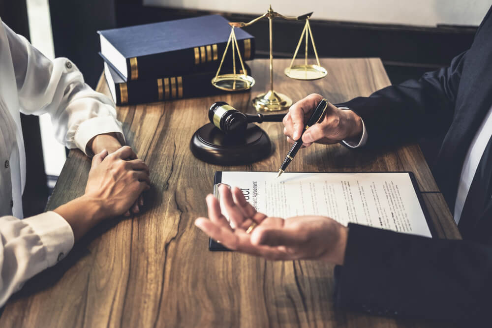 lawyer sitting with client review documents