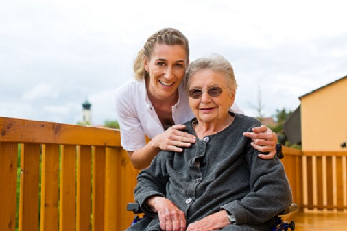 Long-term asset protection - Young nurse and female senior in a wheel chair going for a walk
